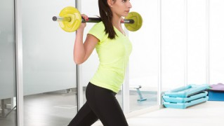 Beautiful sporty woman hold  bar-bell in gym