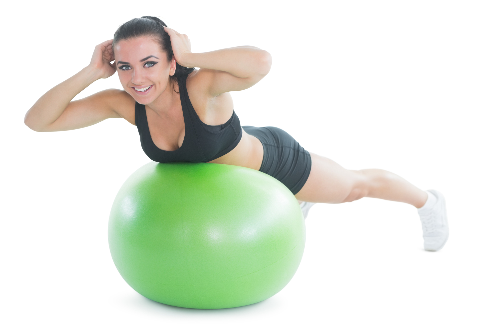 Happy fit woman doing an exercise on a green fitness ball smiling at camera